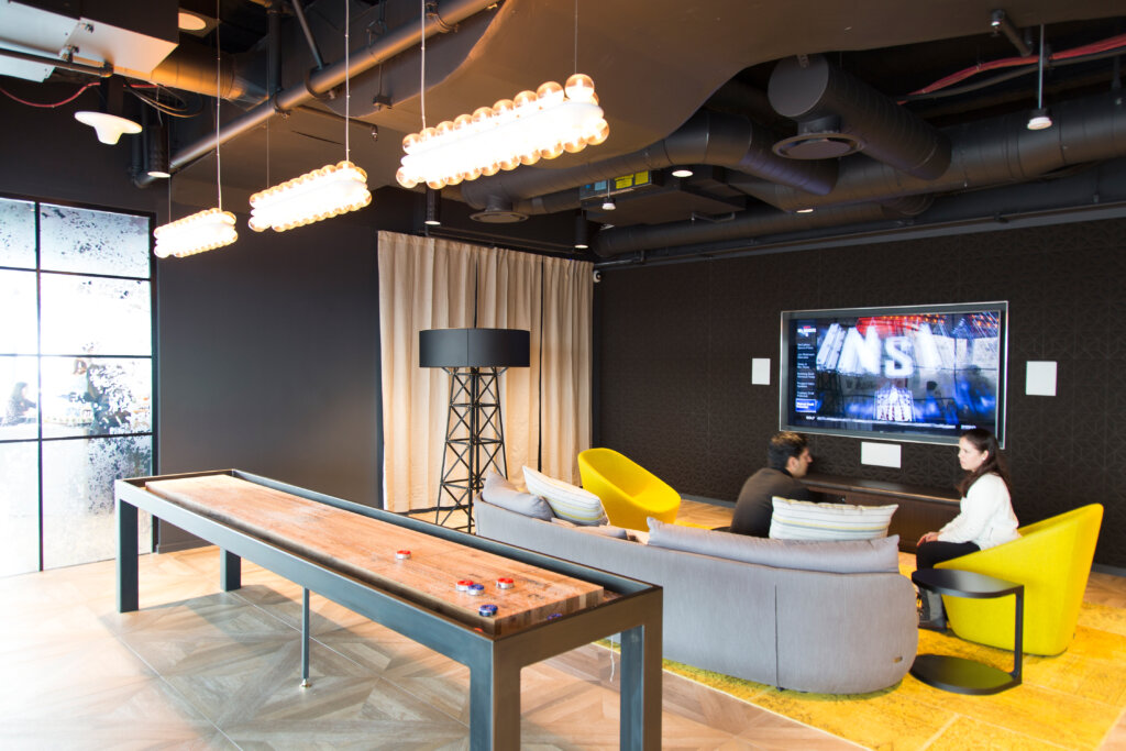 Game room with shuffleboard table and people sitting in chairs in front of a large TV.