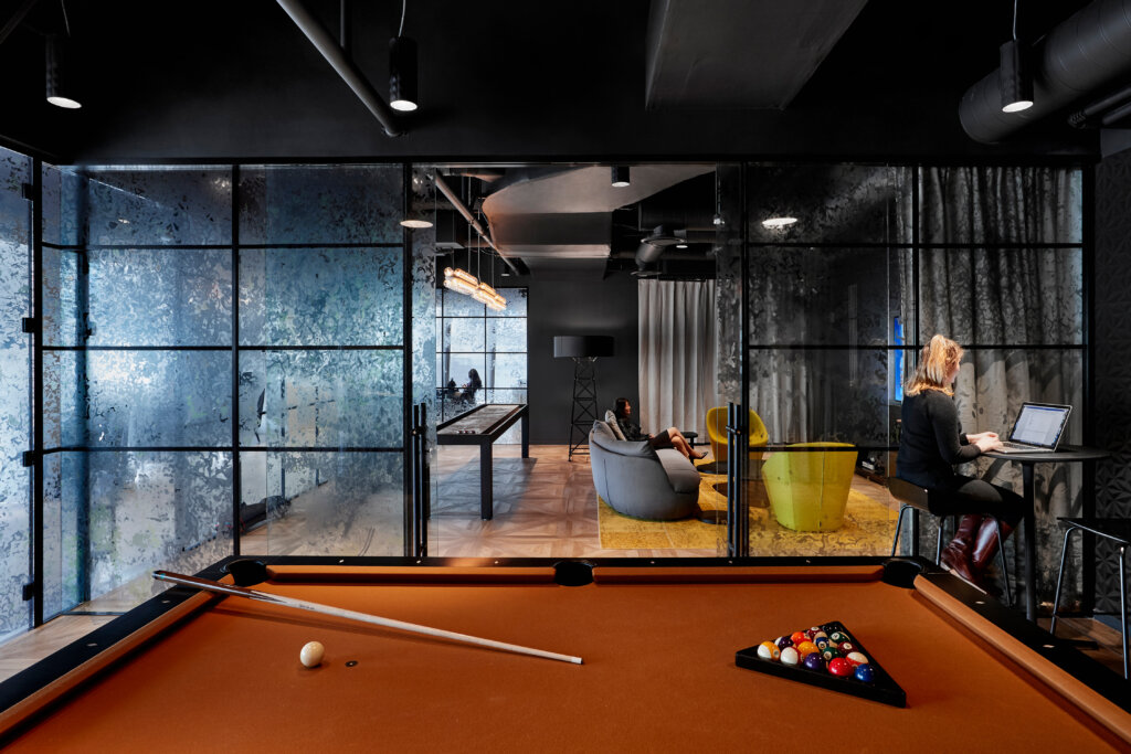 Game room with pool table, chairs, sofa and small work space.