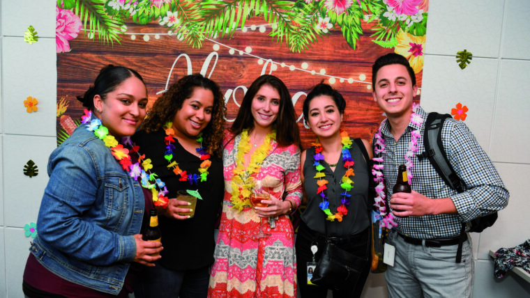 A group of five people wearing leis and holding drinks.