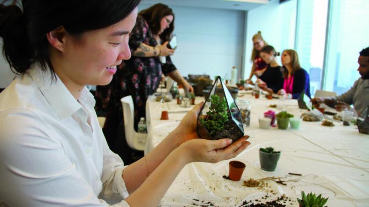 Woman adding soil to succulent terrarium.