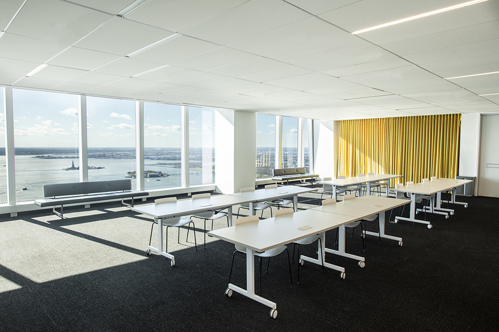 Meeting space with river views and four tables with four chairs and bench seating in front of the windows.